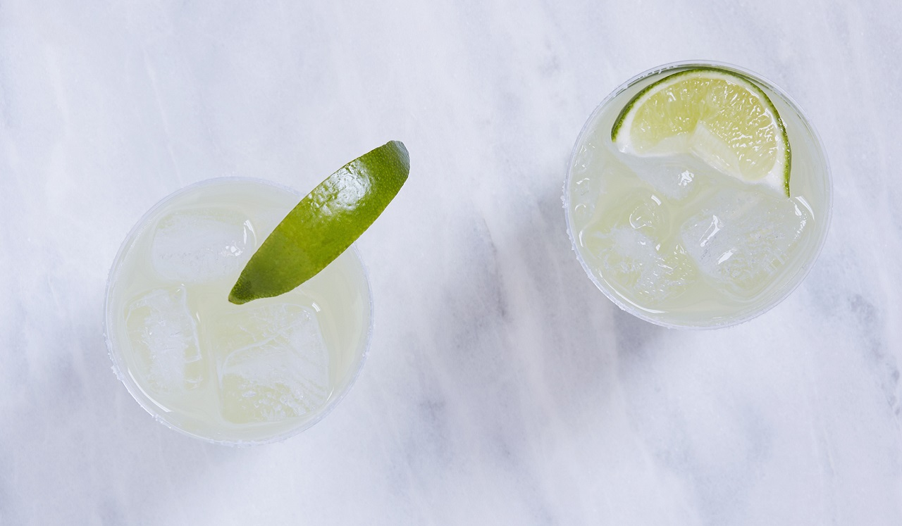 An aerial view of two drinks with limes.