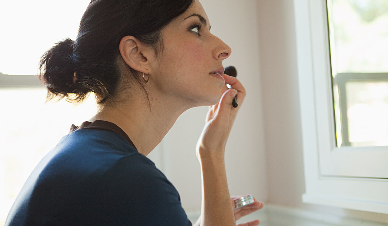 A woman looking in the mirror and doing her make up.