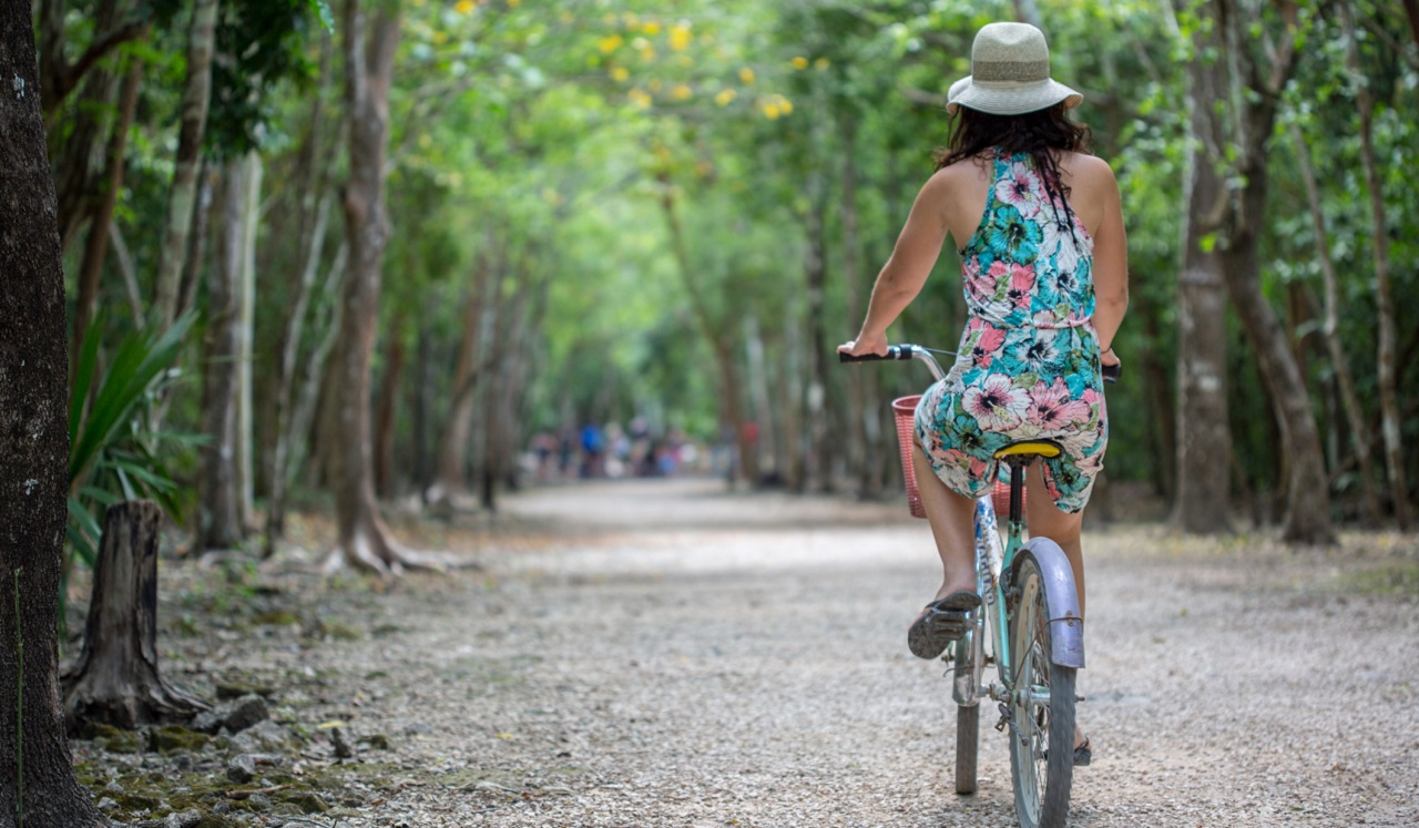 A woman riding a bicycle along a path.