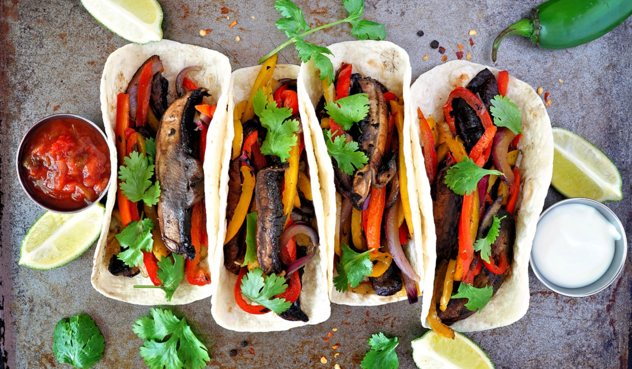 Four tacos stuffed with bell peppers and Portobello mushrooms.