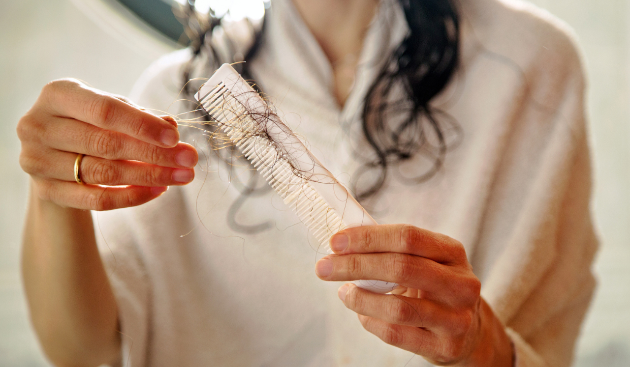 A woman in a bathrobe holding wet, fallen hairs.