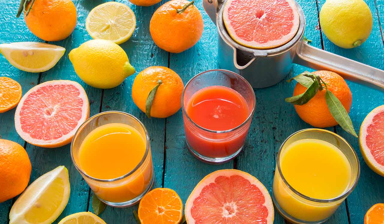 Glasses of juice and surrounded by sliced citrus fruits.