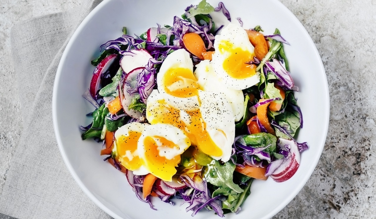 A bowl of salad topped with eggs.