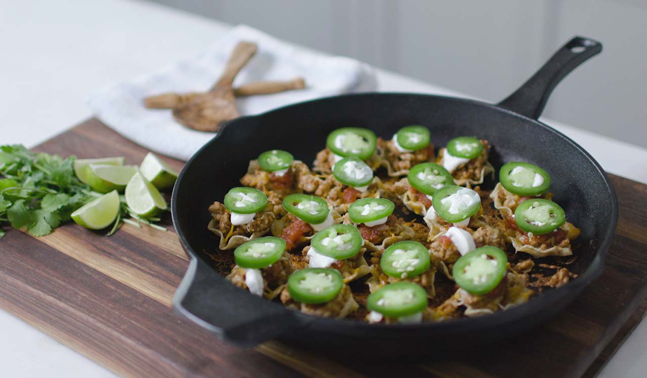 Skillet nachos topped with jalapenos and cheese.
