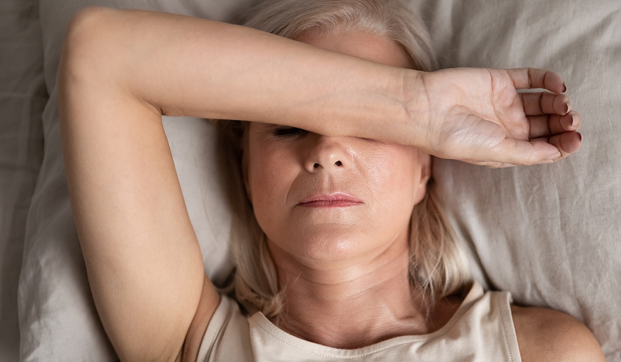 Woman laying down with arm across her head