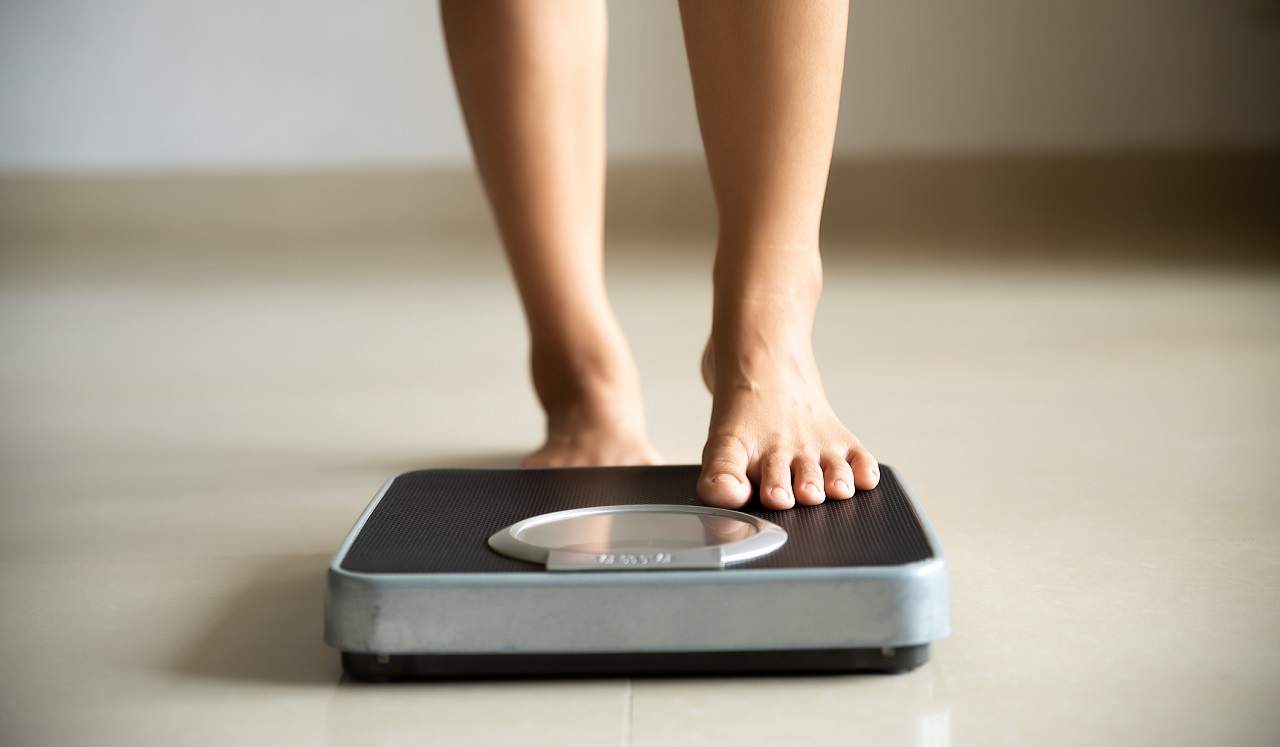 A person's feet stepping on to a scale.