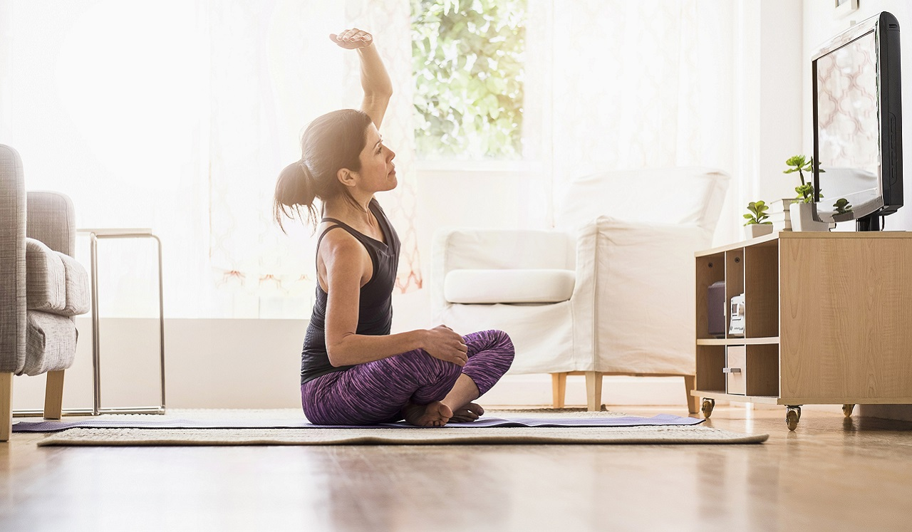 A woman following a yoga practice from her television.