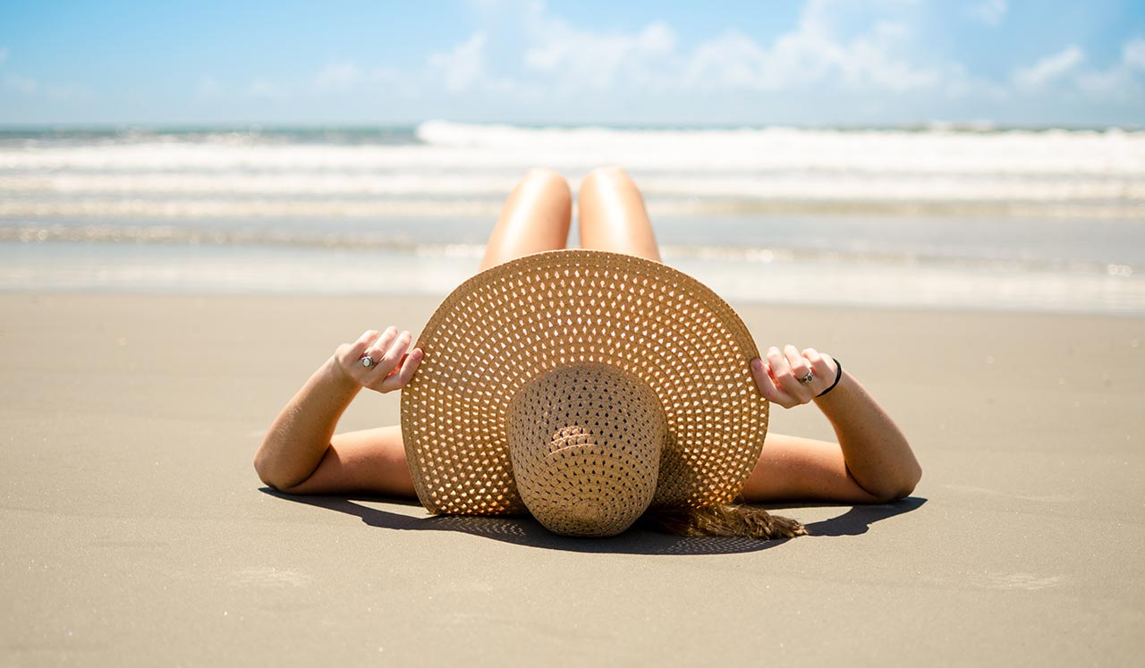 Woman in a hat lying on the beach
