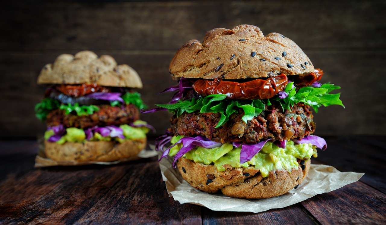 Plant based burgers dressed with lettuce and sun dried tomatoes