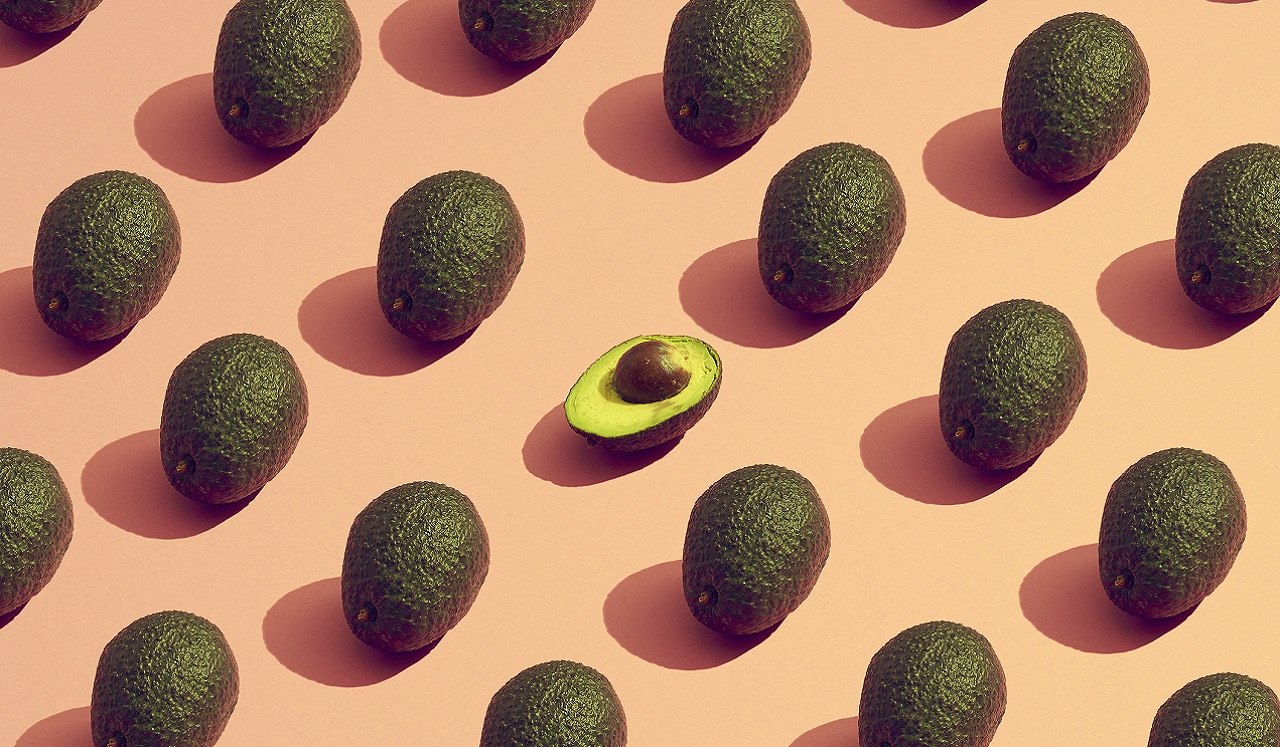 Avocados arranged in a pattern along a pink backdrop