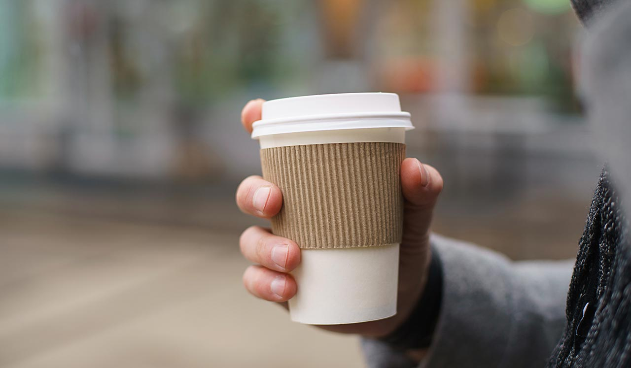 A hand holding a disposable coffee cup.