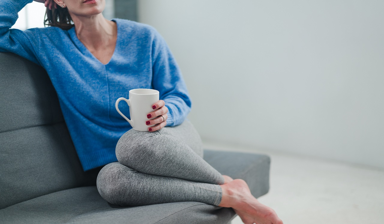 A woman relaxing while holding a cup of tea.