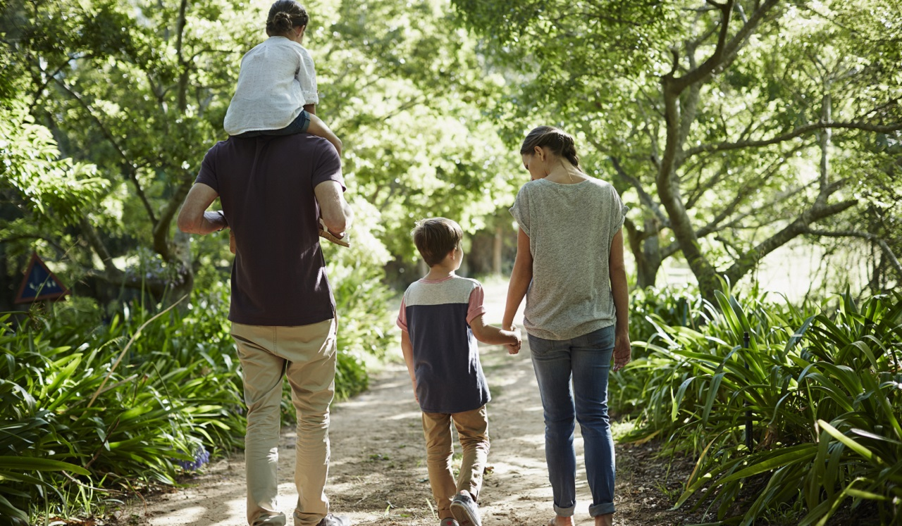 A family of four walking along a trail.