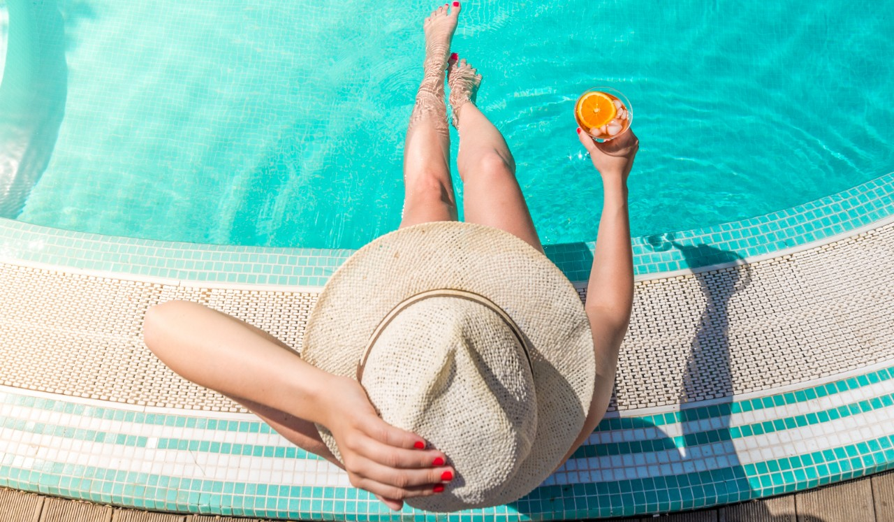 A woman in a brimmed hat sits pool side with her feet in the water.