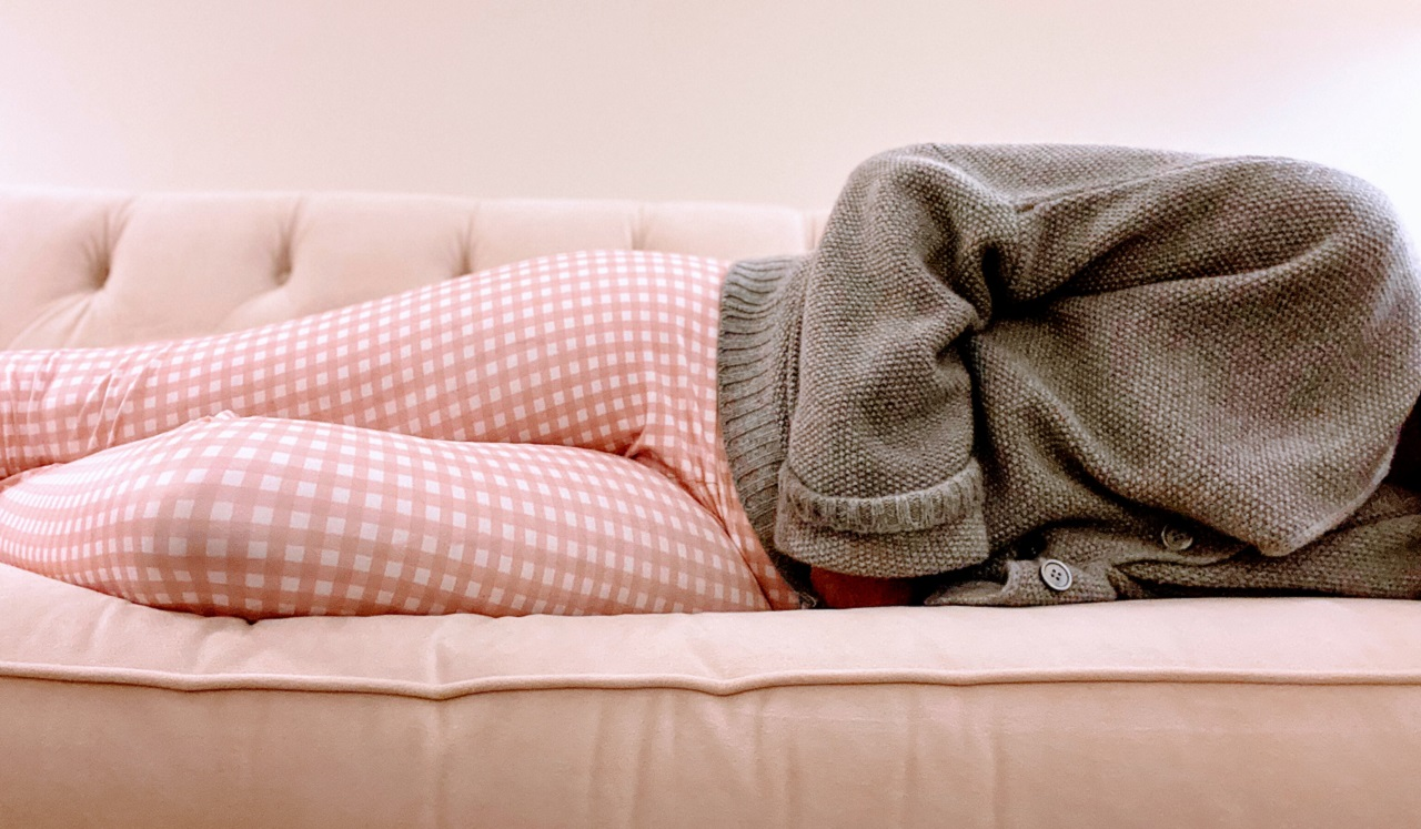 A person in pajamas lying on the couch and holding their stomach.