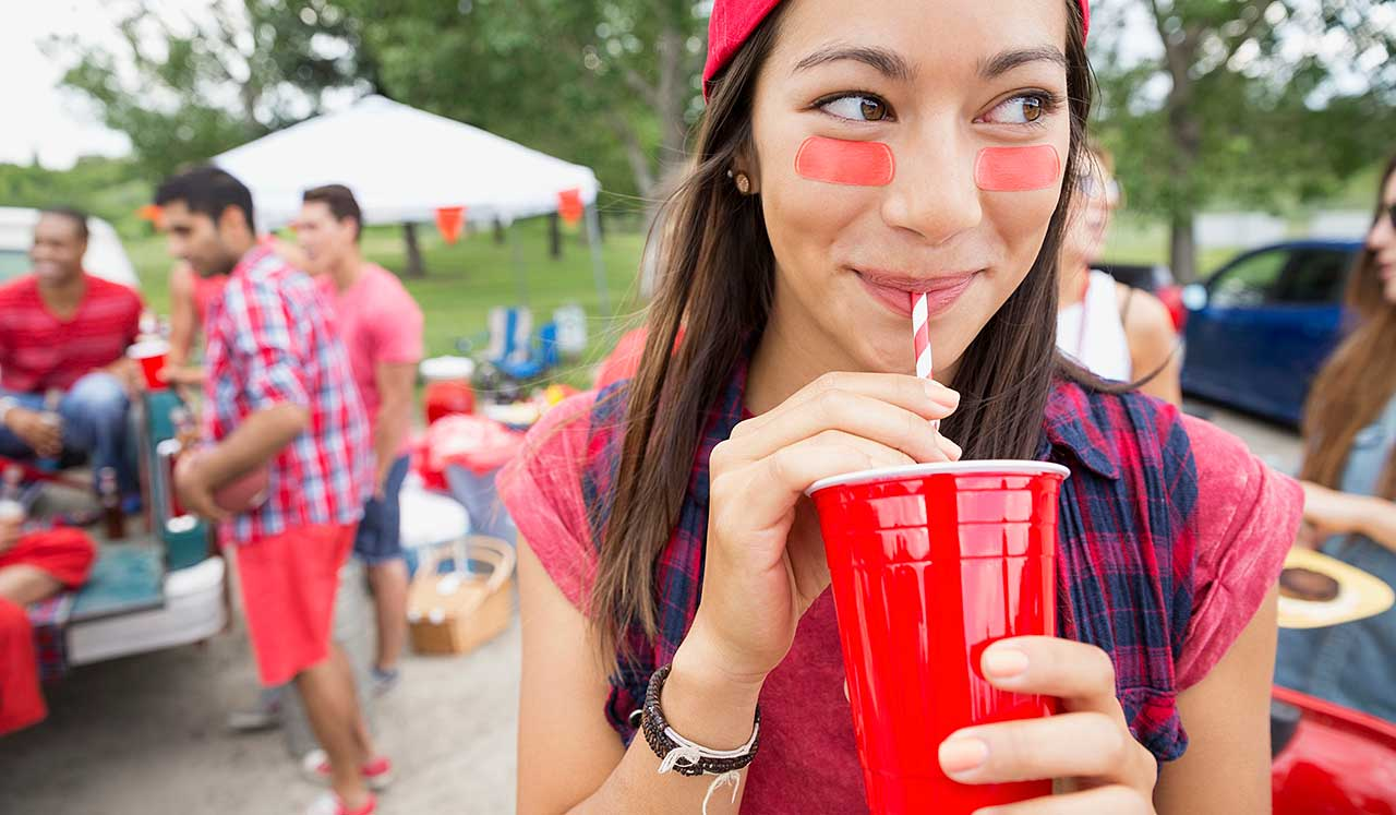 A girl at tailgate is drinking from a solo cup.