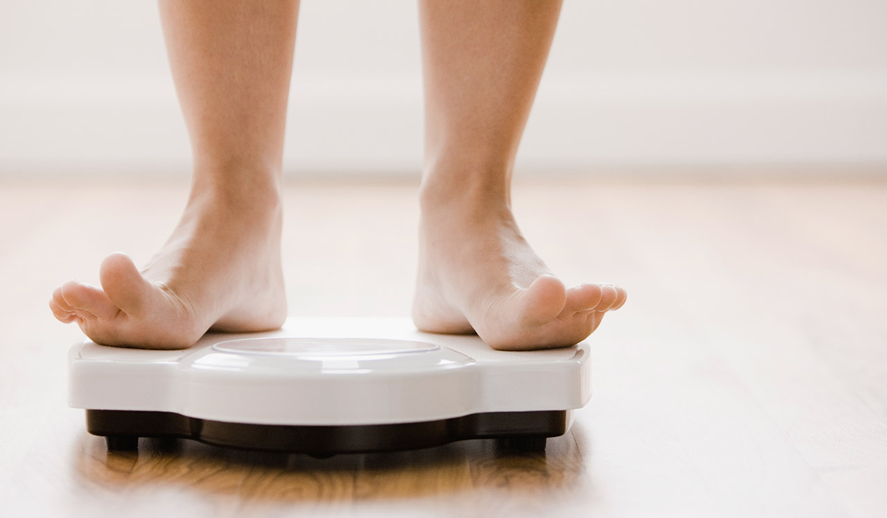 A person steps on to a white bathroom scale.