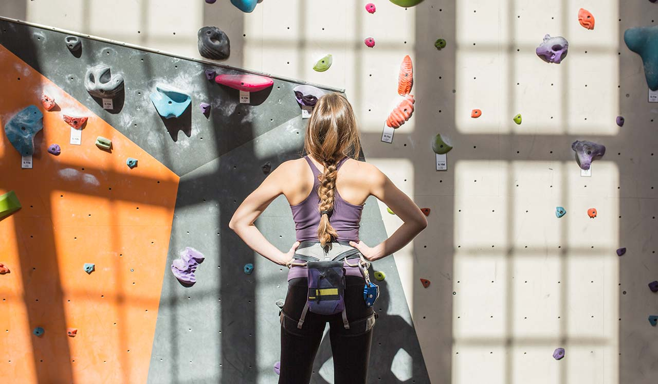 A woman in climbing gear looks up at a climbing rock wall.