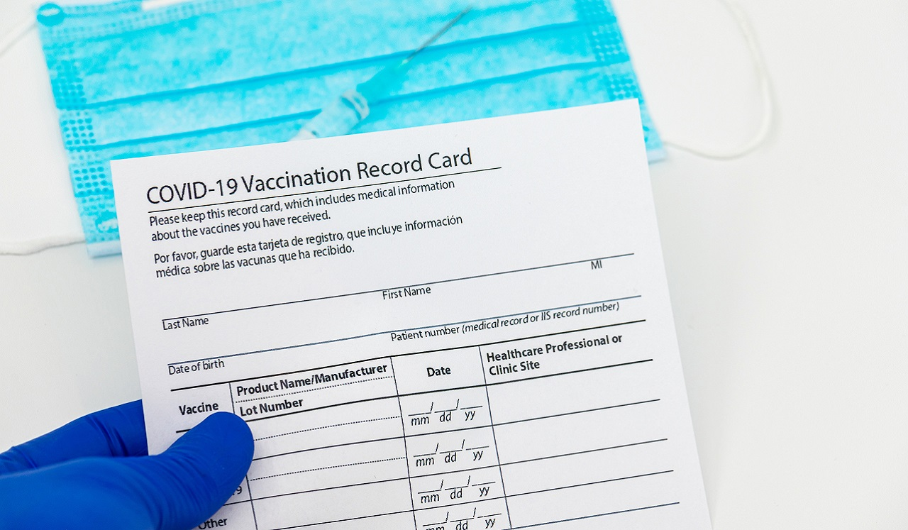 A gloved hand holds a vaccination record card; in the background is a syringe and a medical face mask.