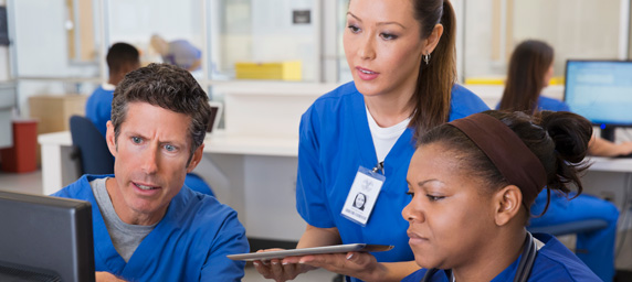 Nurses talking and looking at computer