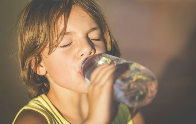 Child drinking water from  a bottle