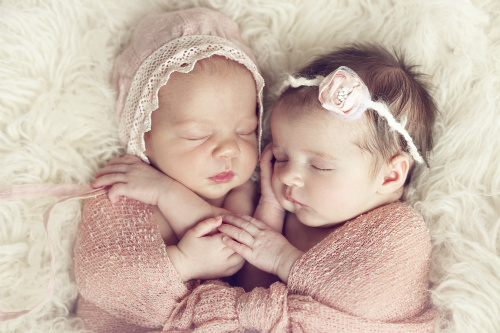 Twin babies sleeping and holding hands