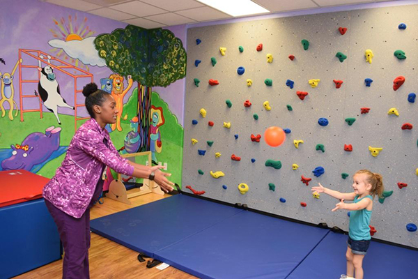 A child and therapist play with a ball in a brightly colored room with a rock wall.
