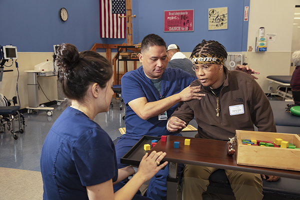A patient works with blocks with the help of therapists.