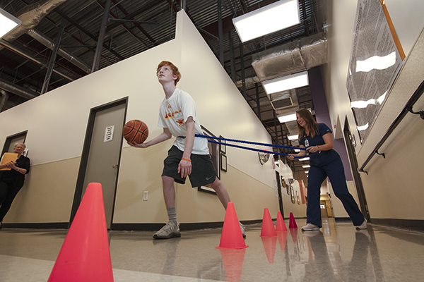 A teenager works with a basketball down the hall.