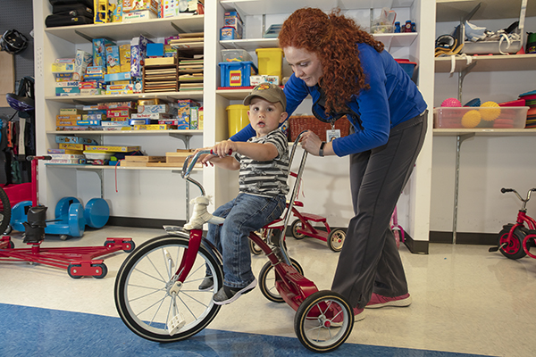 A toddler is assisted while riding a tricycle.