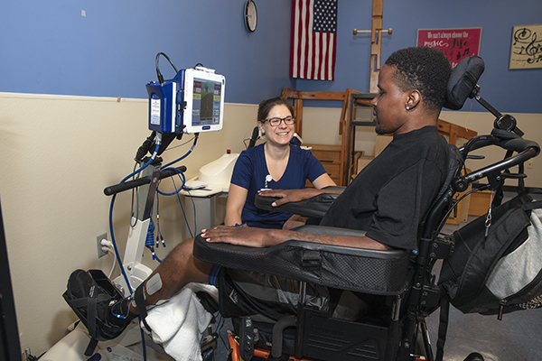 A patient using assistive technology works with therapist.