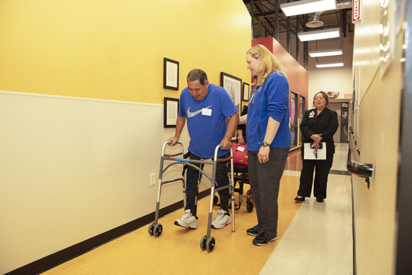 A man uses assistive equipment to walk down the hall.