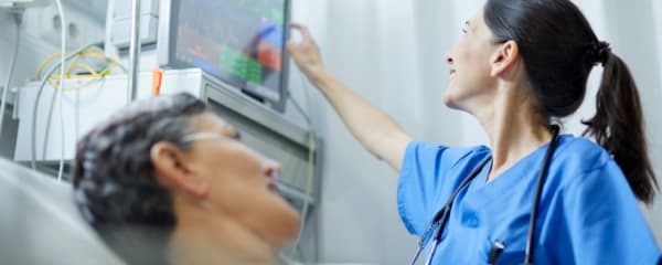 A physician looks at patient's vitals in a hospital setting
